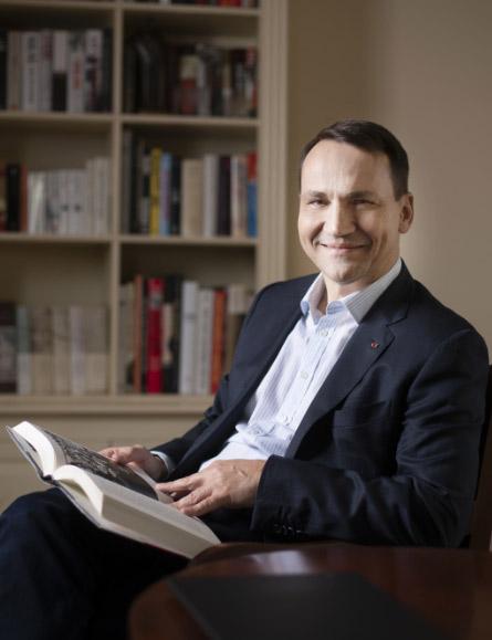 Radosław Sikorski siedzący na fotelu i trzymający w ręku książkę